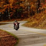 A motorcycle rides the blue ridge parkway near Roanoke surrounded by colorful fall leaves