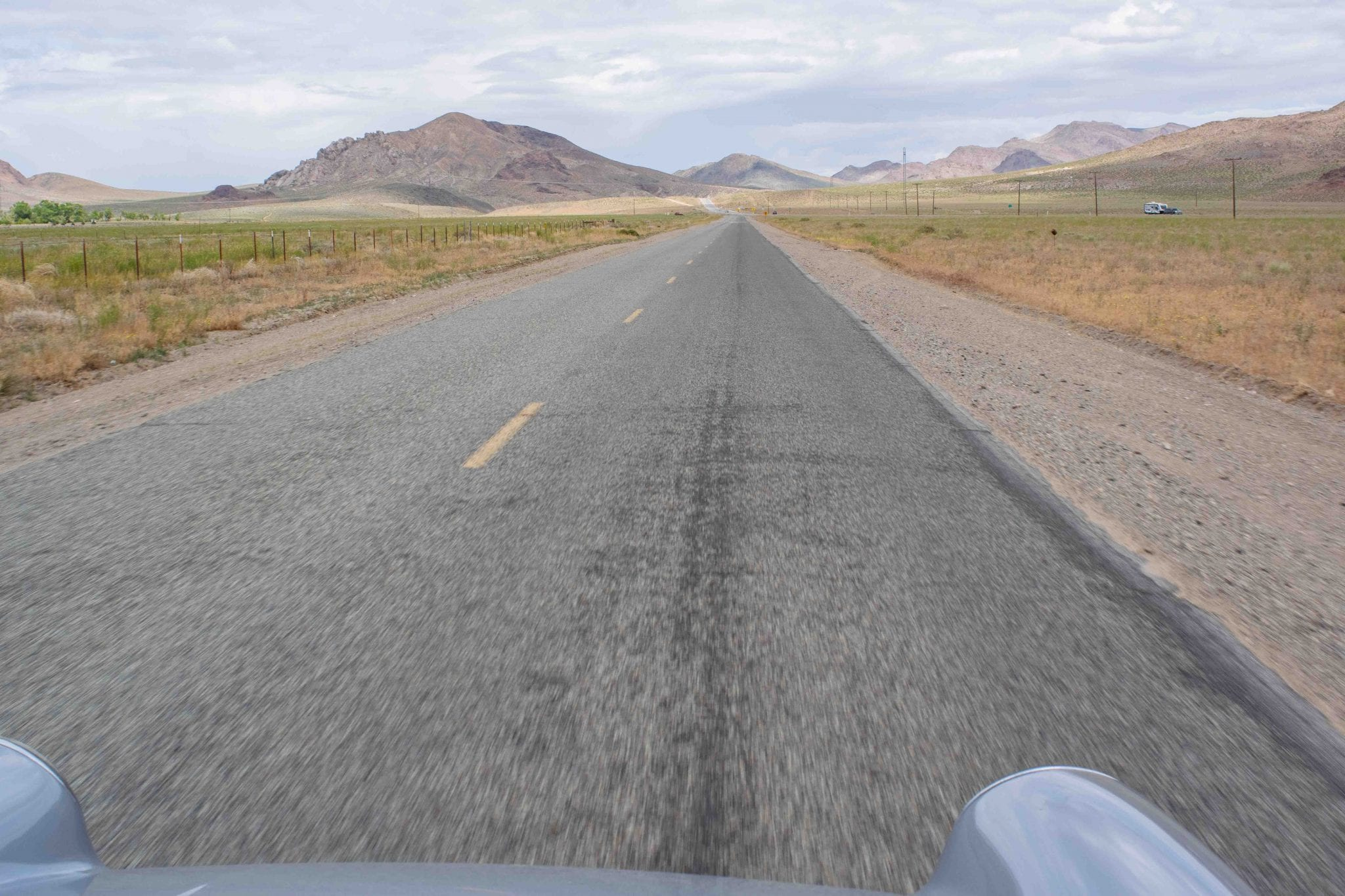 A two lane back road stretches off in the distance towards sandy desert mountains