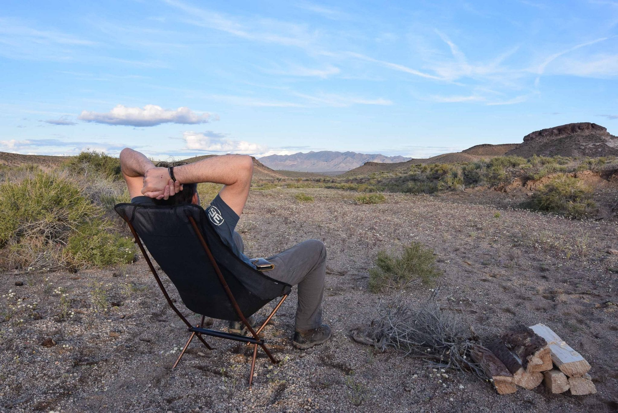 A man relaxes in a camping chair next to a stack of firewood, staring at the distant mountains and desert