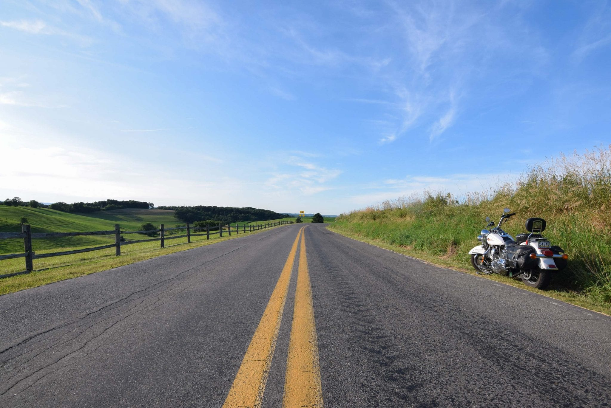 A white Harley Davidson sits on the shoulder of a broad country road under a brilliant blue sky.